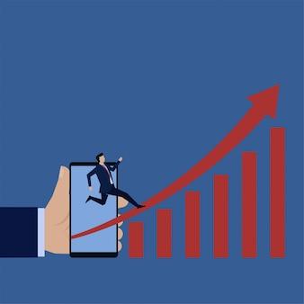 L'uomo d'affari piano di affari passa il grafico in aumento dalle vendite crescenti del telefono con lo smartphone.