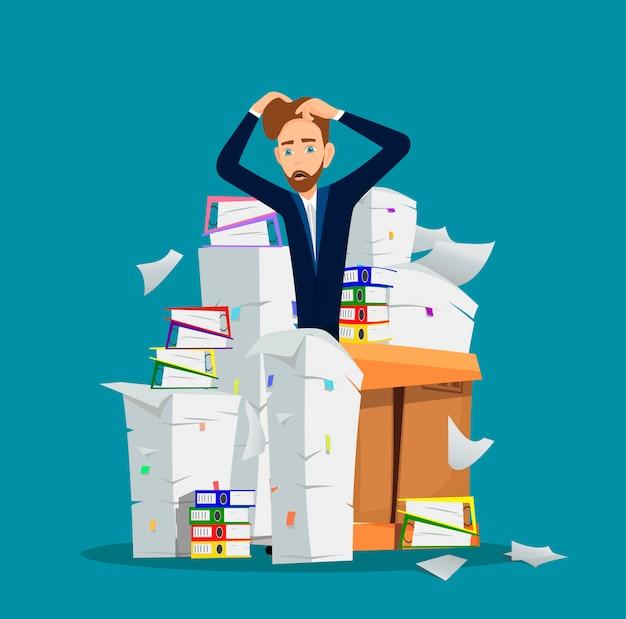 L'uomo d'affari si leva in piedi fra il mucchio dei documenti dell'ufficio