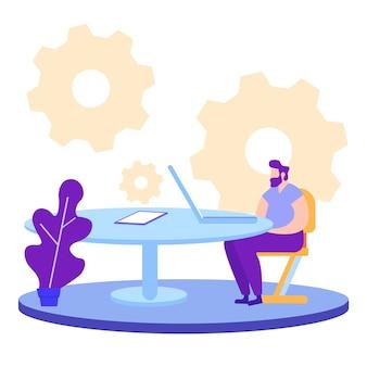 L'uomo si siede sulla sedia vicino al computer portatile.