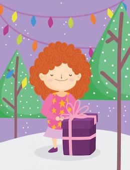 La bambina di buon natale con le luci brutte degli alberi del regalo del maglione nevica all'aperto