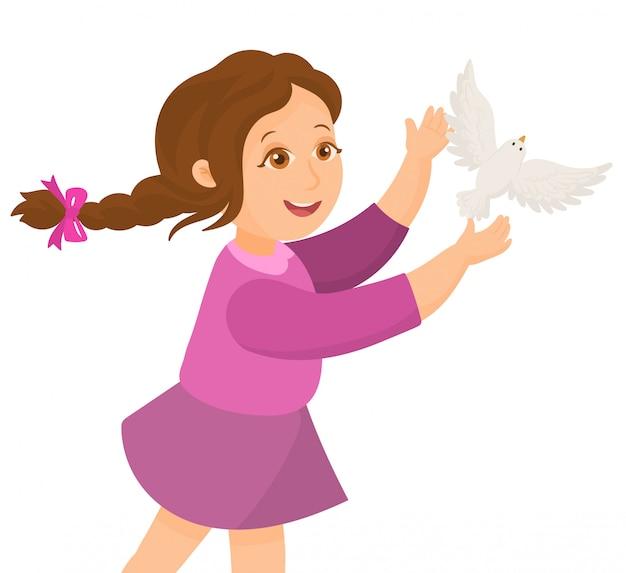 La bambina libera una colomba della pace dalle sue mani
