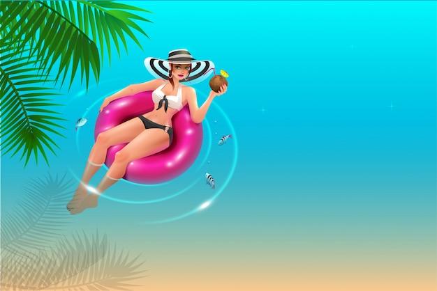 La bella giovane donna in cappello galleggia sul cerchio sull'acqua blu e beve il succo della noce di cocco.