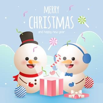 La cartolina d'auguri di buon natale con due pupazzi di neve apre una scatola attuale