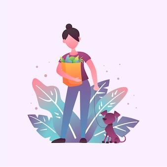La donna cammina con un cane e con un sacchetto della spesa