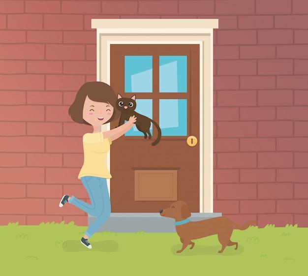 La donna con il piccolo gatto e cane svegli nel giardino della casa