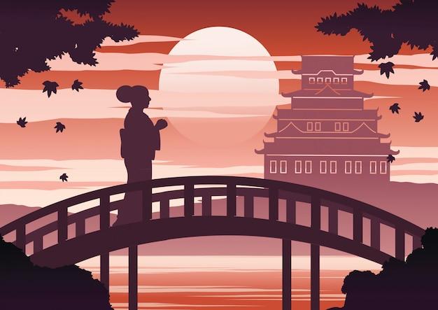 La donna del giappone in vestito dal kimono si leva in piedi sul ponticello