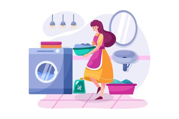 La donna delle pulizie che porta i vestiti alla lavatrice