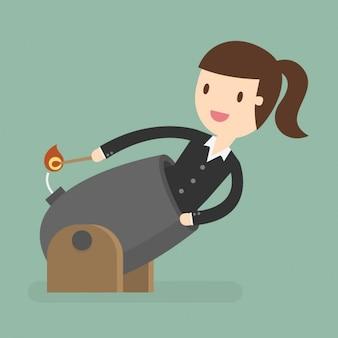 La donna di affari accendere la miccia di un cannone
