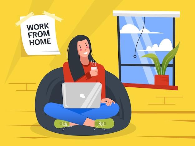 La donna di affari si siede sul sofà e lavora a casa tenendo la tazza di caffè