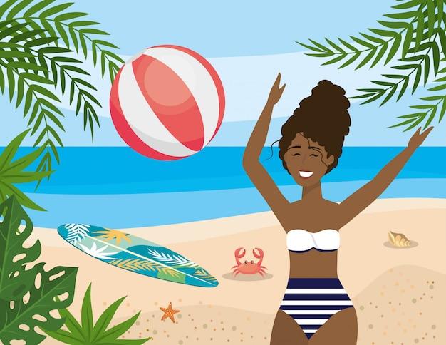 La donna gioca con il beach ball e la tavola da surf con il granchio