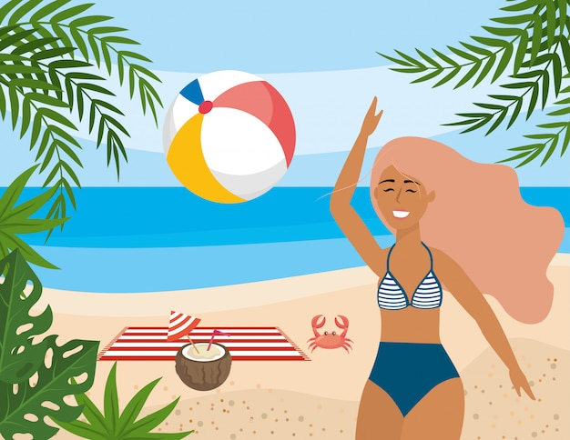 La donna gioca con la sfera della spiaggia e la bevanda della noce di cocco con l'asciugamano