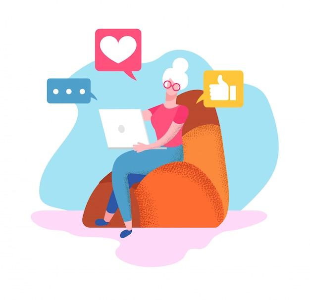 La donna senior si siede sulla poltrona a casa con il computer portatile