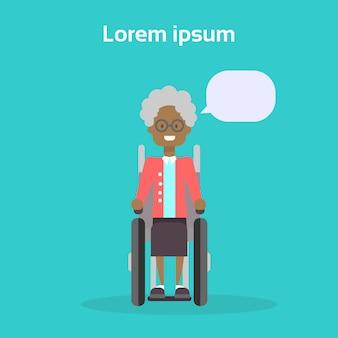 La donna senior sulla sedia a rotelle la donna anziana afroamericana felice sorridente si siede sul concetto di disabilità della sedia a rotelle
