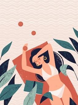 La donna si trova su un tappeto circondato da piante tropicali sulla sabbia.