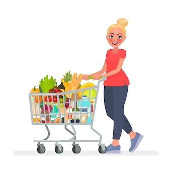 La donna sta portando un carrello della spesa pieno di generi alimentari nel supermercato.