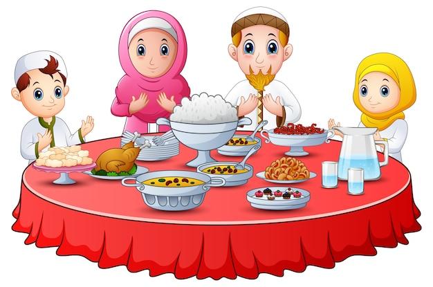 La famiglia musulmana prega insieme prima di rompere il digiuno