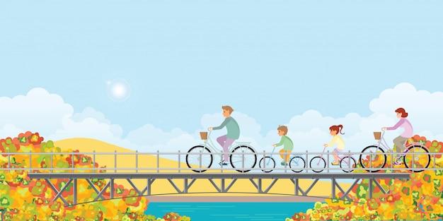 La famiglia sta guidando sulle biciclette sul ponte in autunno.