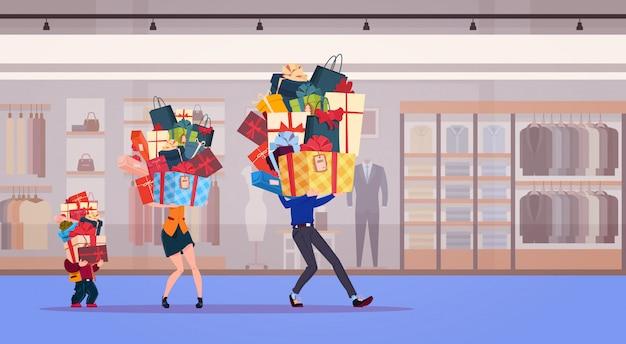 La famiglia trasporta la pila di presente sopra i regali di festa del fondo del negozio ed il concetto stagionale di vendita