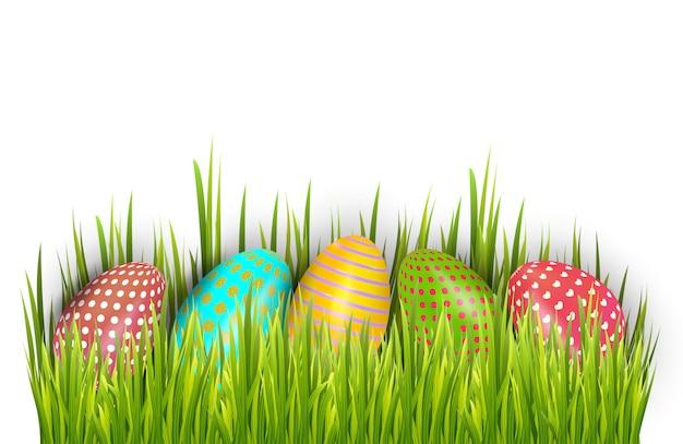 La fila di pasqua ha dipinto le uova nascoste in erba verde e isolate su fondo bianco