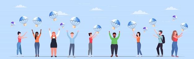 La gente che cattura le scatole dei pacchi che cadono con il paracadute dal trasporto del cielo pacchetto di spedizione posta aerea espresso concetto di consegna postale orizzontale integrale