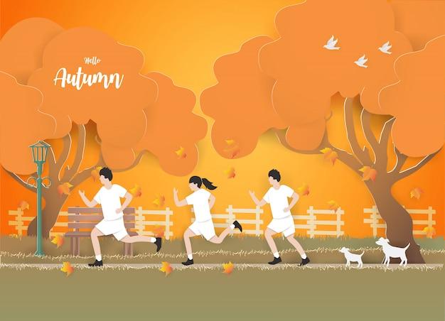 La gente che corre sull'erba nel fondo di autunno.