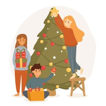 La gente che decora i precedenti di stagione invernale dell'albero di natale