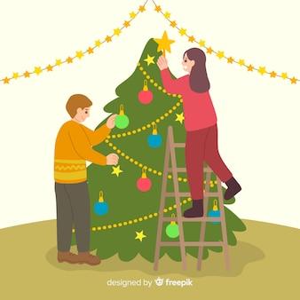 La gente che decora l'albero di natale all'interno