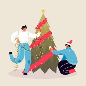 La gente che decora l'albero di natale con le luci della stringa