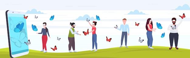 La gente che indossa gli occhiali digitali mescola la gente che tocca la farfalla di volo del vr dallo schermo integrale dello smartphone la visione della realtà virtuale concetto la tecnologia integrale orizzontale