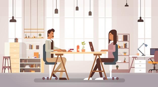 La gente di affari indiana raggruppa il lavoro nel posto di lavoro moderno del centro creativo di coworking dell'ufficio