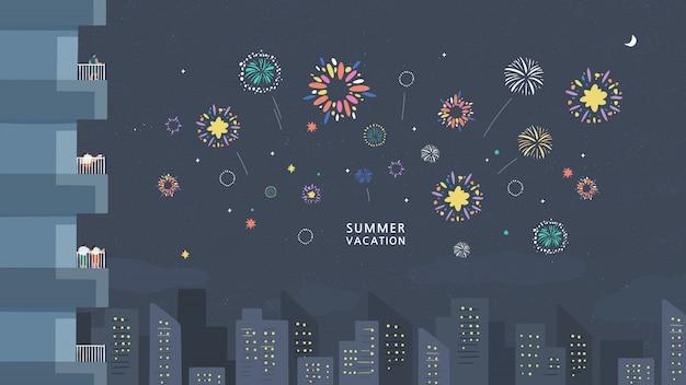 La gente guarda i fuochi d'artificio che si esibiscono nel buio del cielo serale e festeggiano le vacanze contro gli edifici della città.