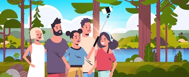 La gente raggruppa in foresta facendo uso del bastone del selfie che prende la foto sulla macchina fotografica dello smartphone che fa un'escursione gli amici di concetto che stanno insieme il ritratto orizzontale del ritratto del fondo