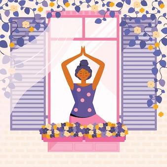La giovane donna pratica la meditazione e lo yoga a casa. la persona alla finestra è impegnata nello sport. trascorrere del tempo a casa. tempo libero in quarantena. facciata della casa con una finestra e fiori.