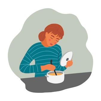 La giovane donna sta cucinando la zuppa