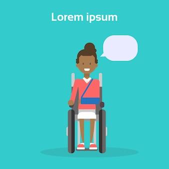 La giovane donna sulla sedia a rotelle la donna afroamericana felice disabile sorridente si siede sul concetto di disabilità della sedia a rotelle