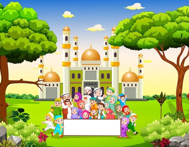 La grande famiglia felice tiene lo striscione bianco vicino alla moschea