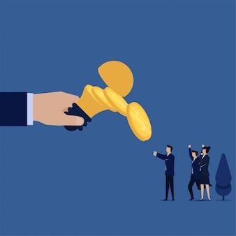 La lampada e le monete piane della tenuta della mano di concetto di affari cadono da esso metafora di valore di idee.
