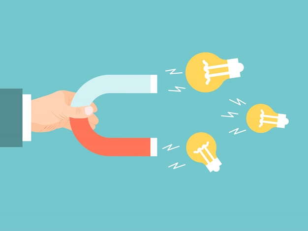 La mano dell'uomo d'affari con il magnete attira le lampadine. lampadina magnetica per idee attraenti.