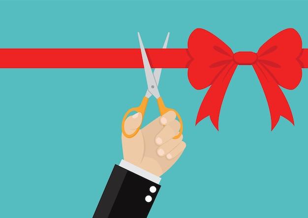 La mano dell'uomo d'affari con le forbici taglia il nastro rosso