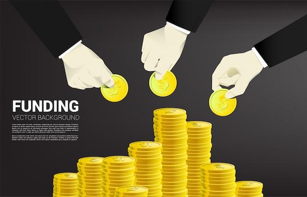 La mano dell'uomo d'affari ha messo i soldi sulla pila di soldi.