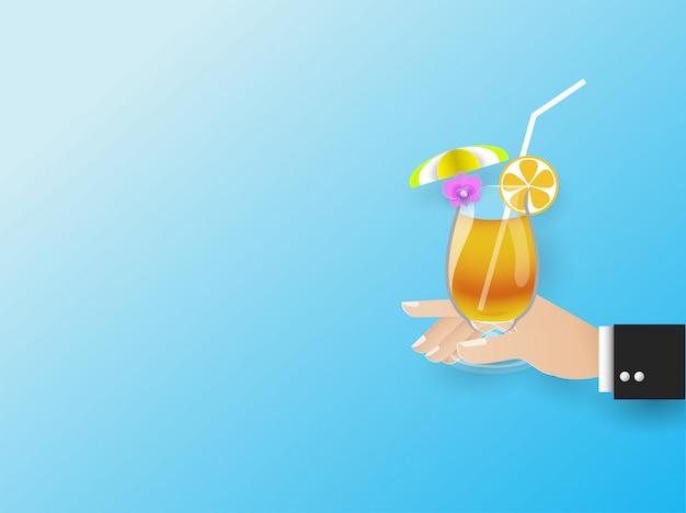 La mano dell'uomo d'affari in possesso di un bicchiere di succo d'arancia con un ombrello giallo e fiori sul vetro, estate