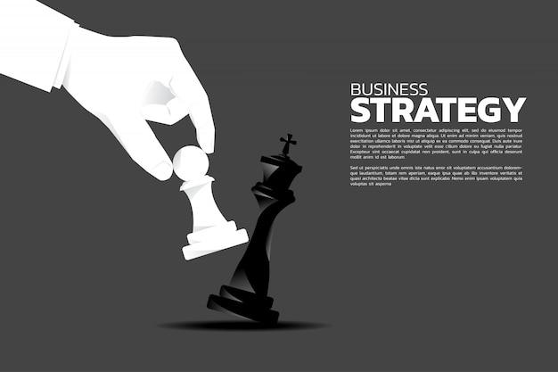 La mano dell'uomo d'affari prende uno scacco matto sul gioco della scacchiera