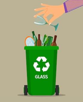 La mano della donna getta spazzatura di vetro