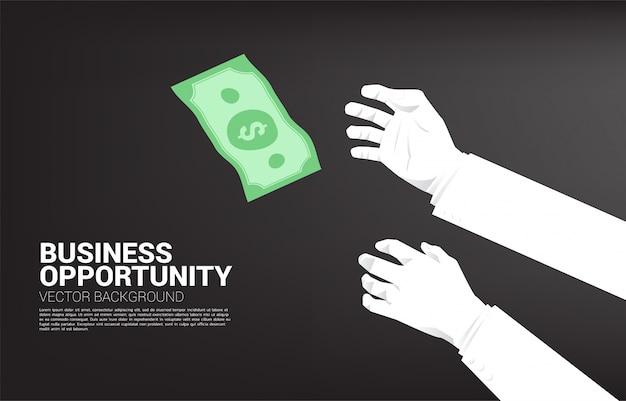 La mano di due uomini d'affari prova a afferrare i soldi che cadono dal cielo. concetto per opportunità di business e concorrenza.