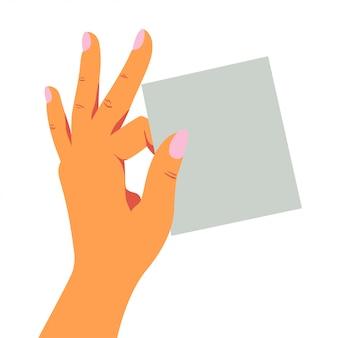 La mano femminile tiene giocosamente un foglio bianco di carta per appunti con due dita.