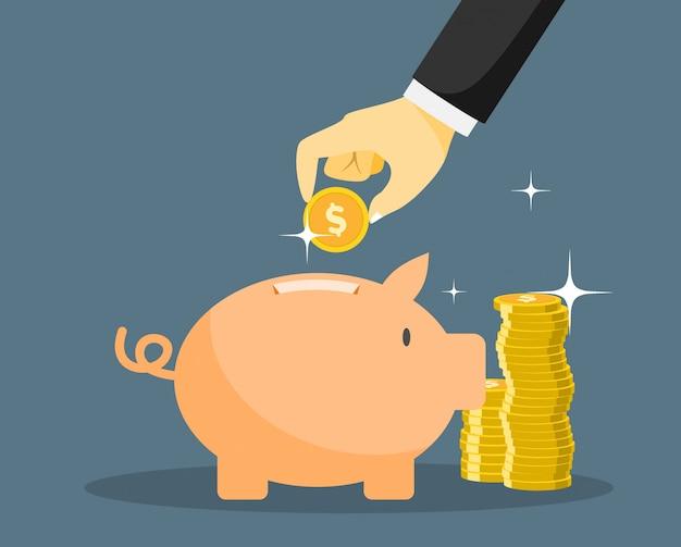 La mano mette una moneta in una banca di maiale.