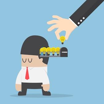 La mano prende la lampadina dell'idea dalla testa dell'uomo d'affari