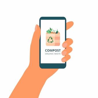 La mano tiene il telefono cellulare con il concetto verde di compostaggio sul display.