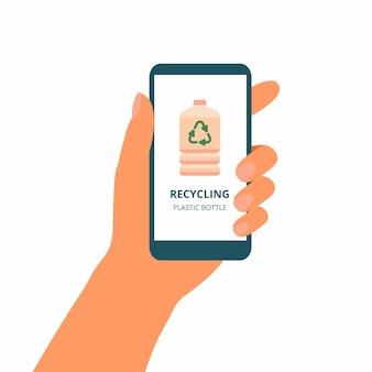 La mano tiene il telefono cellulare con il concetto verde di riciclare le bottiglie di plastica sul display
