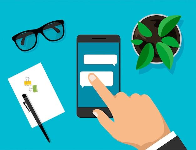 La mano tiene smartphone con finestre di dialogo e fare clic su di esso. telefono con bolle di messaggistica sul display. vista dall'alto dell'area di lavoro. scrivania moderna da lavoro in stile trendy. illustrazione.